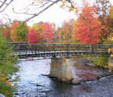 Historic Truesdell truss bridge flanked by autumn colors in Tilton